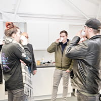 Mitarbeiter des TeleTeams stehen im Kreis zusammen und trinken Kaffee