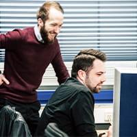 Zwei Mitarbeiter des TeleTeams schauen lächelnd auf einen Monitor