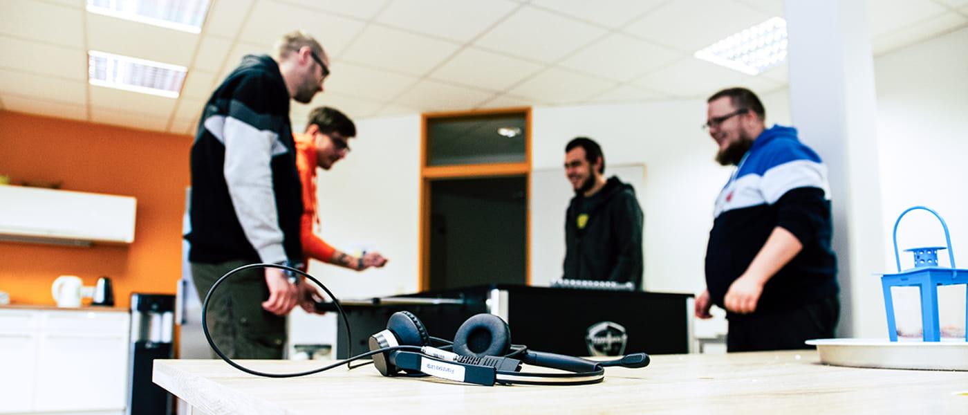 Bild von einem Headset. Im Hintergrund sind 4 Personen zu erkennen, die Tischkicker spielen