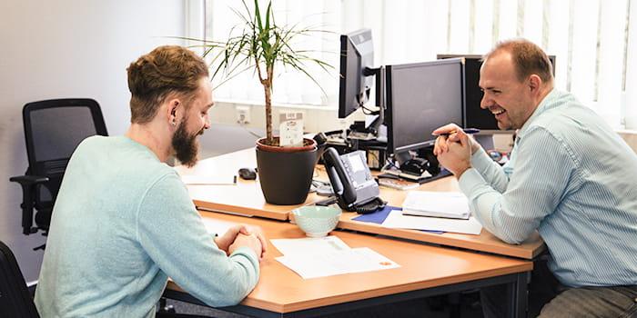 Bild von einem Vier-Augen-Gespräch. Beide Herren lachen.