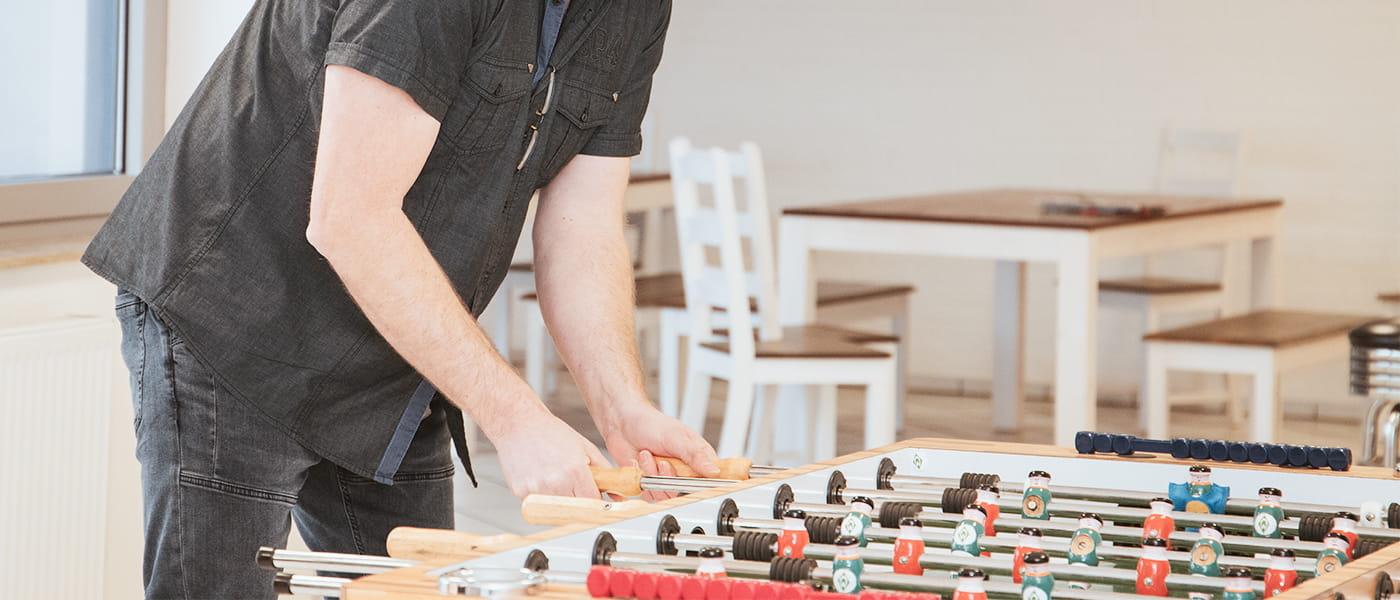 Bild von einem Mann der Tischkicker spielt.