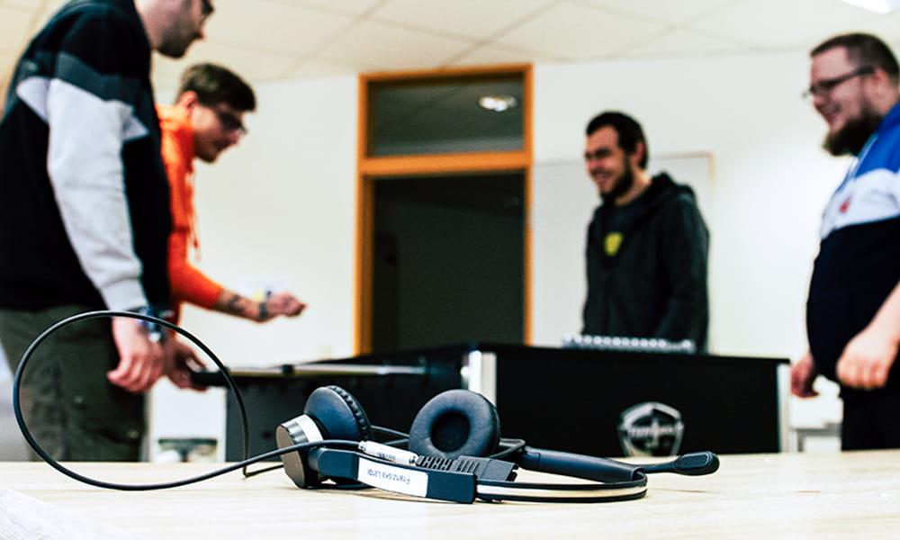 Bild von einem Headset. Im Hintergrund sind 4 Personen zu erkennen, die Tischkicker spielen.