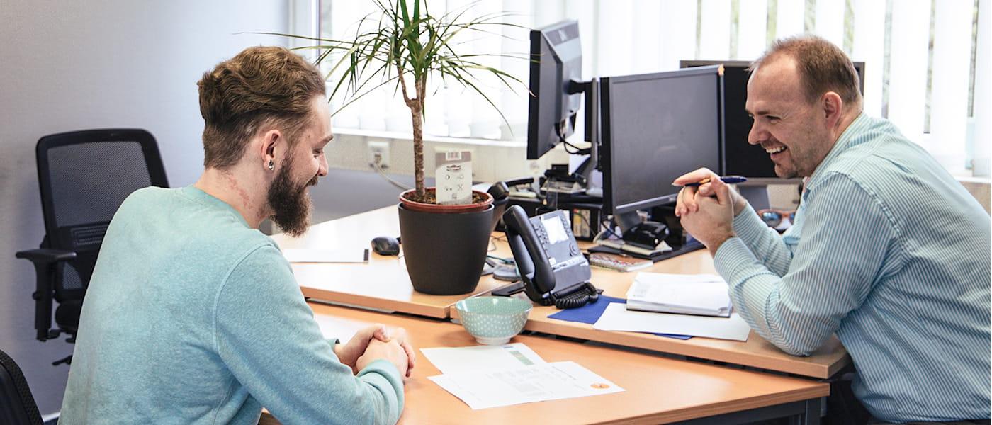 Bild zwei lächelnden TeleTeam Mitarbeitern in einem Vier-Augen-Gespräch.