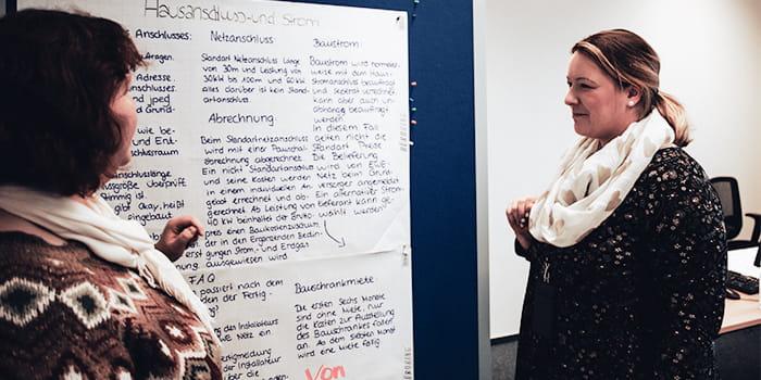 Zwei Frauen stehen vor einer vollgeschriebenen Pinnwand
