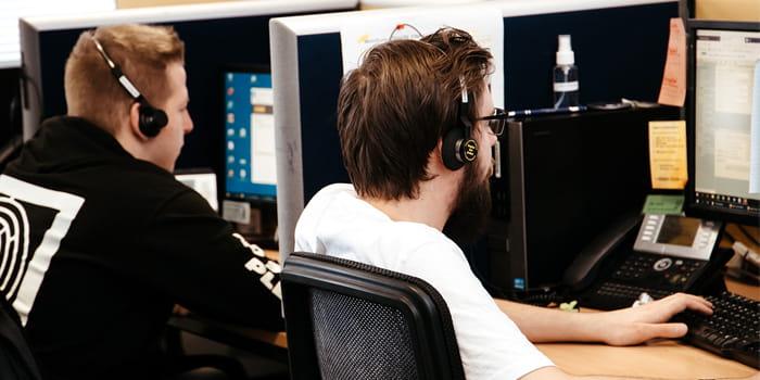 Bild von zwei TeleTeam Mitarbeitern bei der Arbeit.