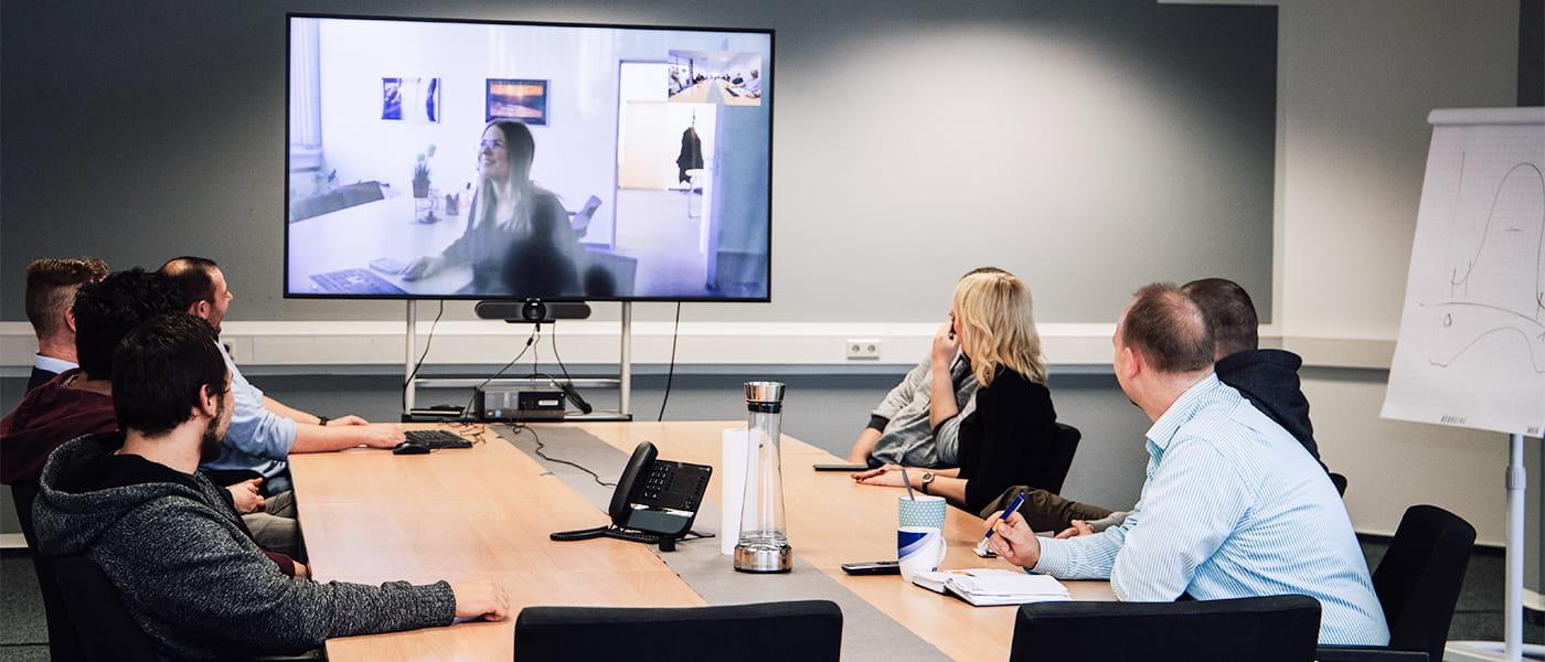 Bild von einem Meeting mit 7 anwesenden und einer durch Video zugeschalteten Person