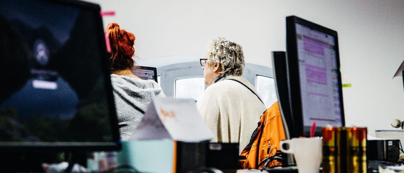 Bild von zwei Männern, die auf einen Bildschirm schauen. Der eine Mann erklärt dem anderen etwas.